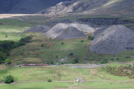 A West Highland Railway train is dwarfed by the slate heaps near Rhyd-Ddu