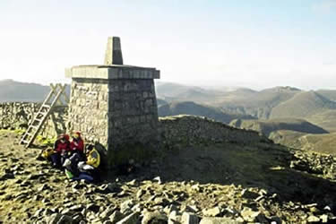 Walkers shelter from the gale on Slieve Donard summit with its oversize trig point
