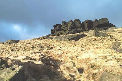 Edale Rocks stand out against a dark wintry sky