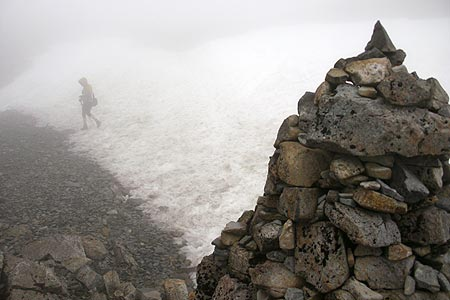 Walker crosses snowfield on path up Ben Nevis